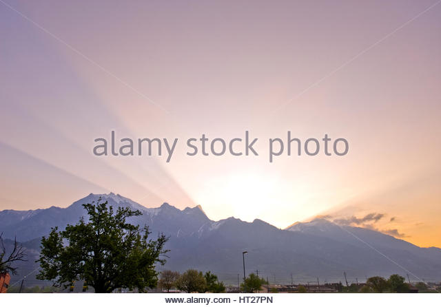 Unusual early morning sun rays with soft pastel colours,over the misty alpes in Switzerland. Sunrise in summertime. - Stock Image