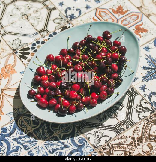 Fresh sweet cherries in plate over oriental ceramic tiles background - Stock Image