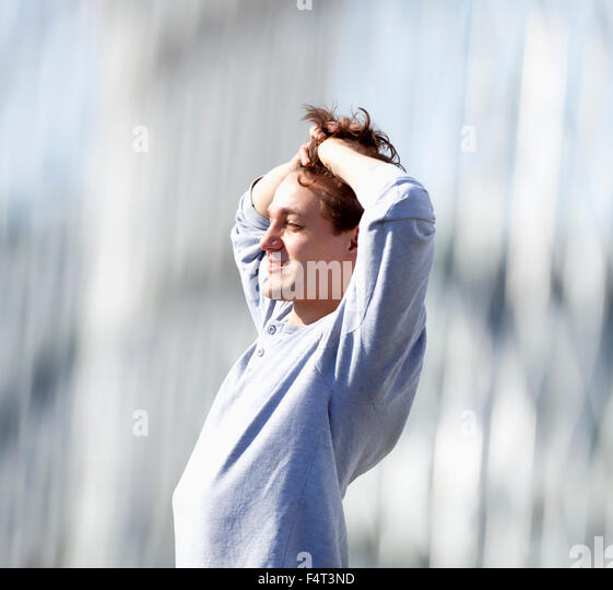 Young Man Standing, Fingers in Hair, Feeling Happy - Stock Image