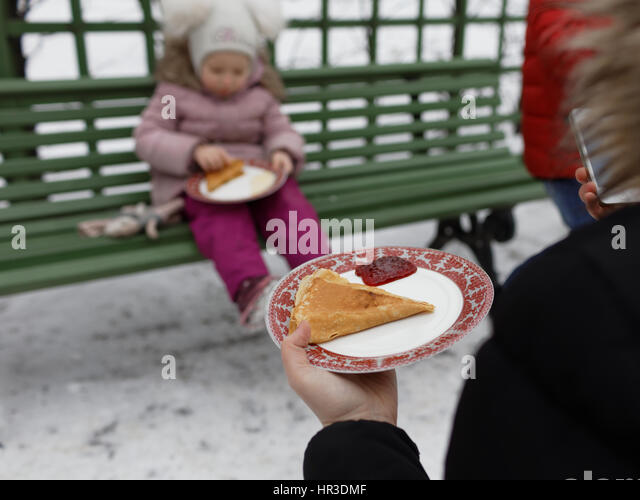 St. Petersburg, Russia, 26th February, 2017. People eating blinis during Shrovetide celebrations in the Summer Garden. - Stock Image
