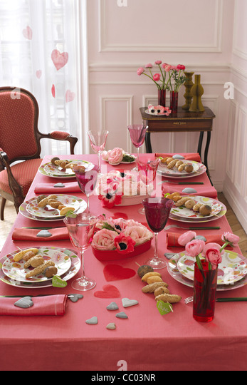 Table with place settings and food in plates - Stock Image