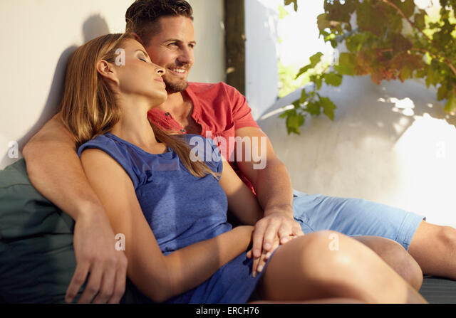 Shot of a loving couple sitting beside each other on patio. Young man and woman in love sitting together on couch - Stock-Bilder