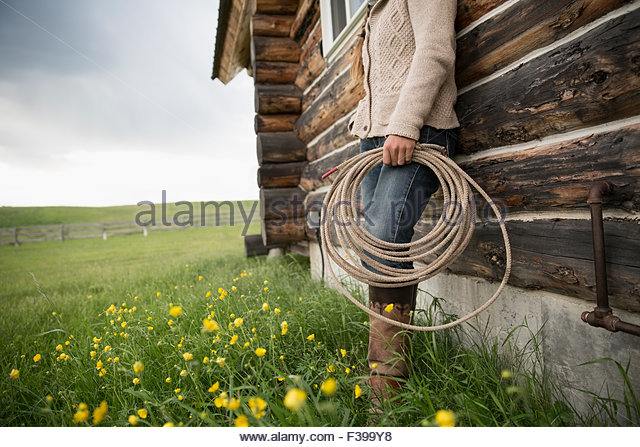 Female rancher holding coiled rope against cabin wall - Stock Image
