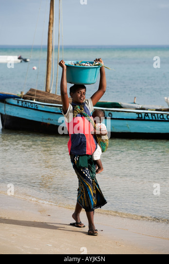 African woman with baby carrying bucket filled with crab on head Dhow sailing boat in background Benguerra Island - Stock Image