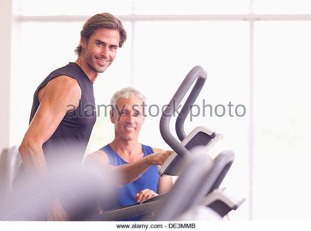 Men talking on treadmill in gymnasium - Stock Image