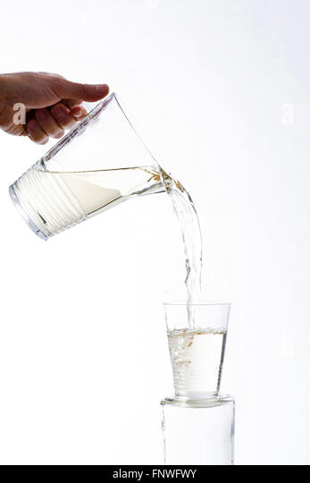 White wine poured from a brimming jug vigorously spouting from a glass, on a white background - Stock Image