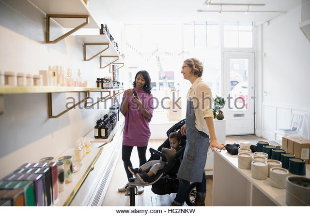 Female shop owner helping mother and son with home fragrances in shop - Stock Image