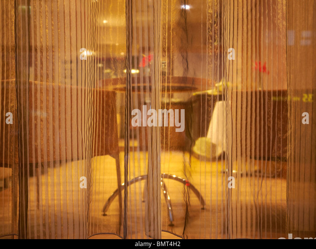Voile curtain in window obscuring what's behind. - Stock Image
