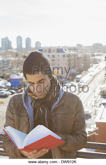 Man reading book outdoors - Stock Image