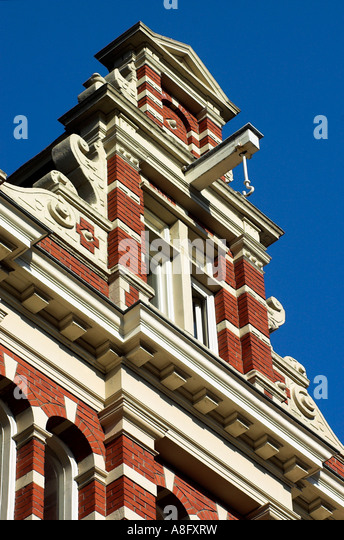 An ornate gabled house with the roof hooks used for moving heavy items in and out of houses in Amsterdam - Stock Image