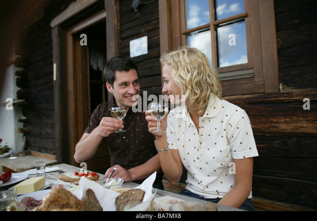 Young couple drinking white wine, Heiligenblut, Hohe Tauern National Park, Carinthia, Austria - Stock Image
