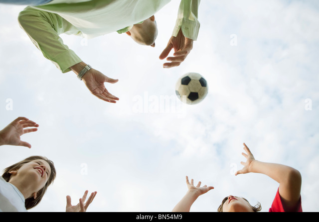 Father and sons playing with soccer ball, low angle view - Stock Image