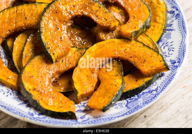 Roasted slices of pumpkin on a serving plate - Stock Image