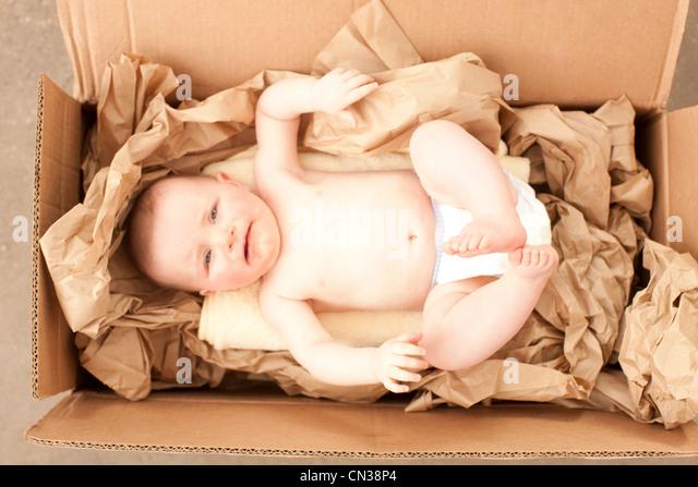 Baby girl in a cardboard box - Stock Image