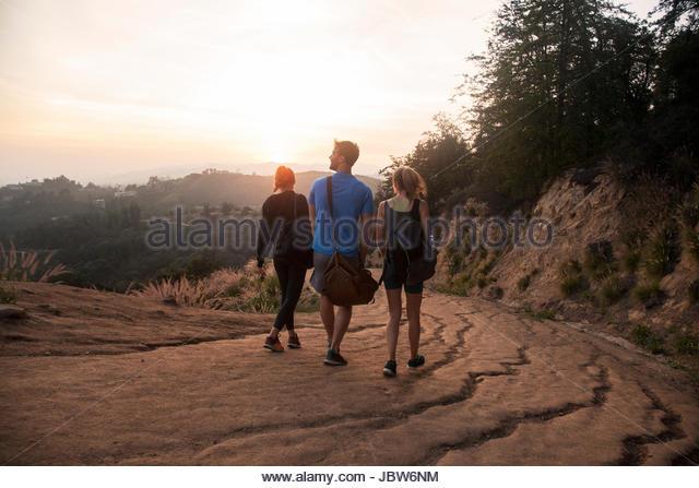 Three friends outdoors, wearing sports clothing, walking along rural road, rear view - Stock-Bilder