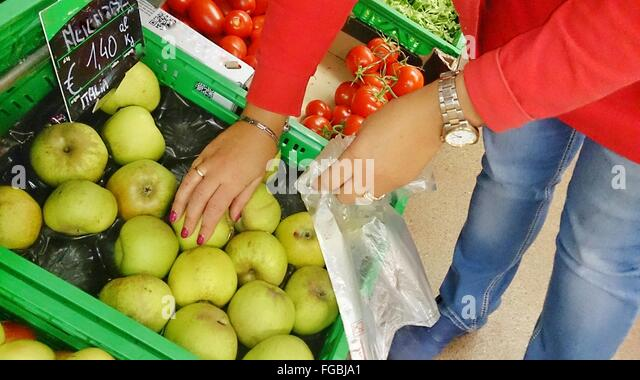 Midsection Of Woman Selecting Apples At Market - Stock Image