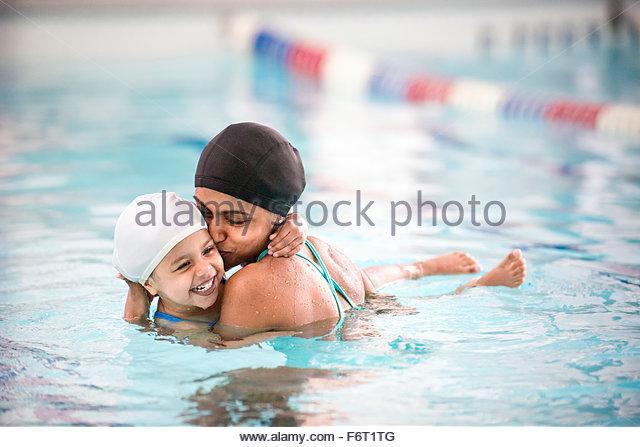 Mother kissing daughter in swimming pool - Stock-Bilder