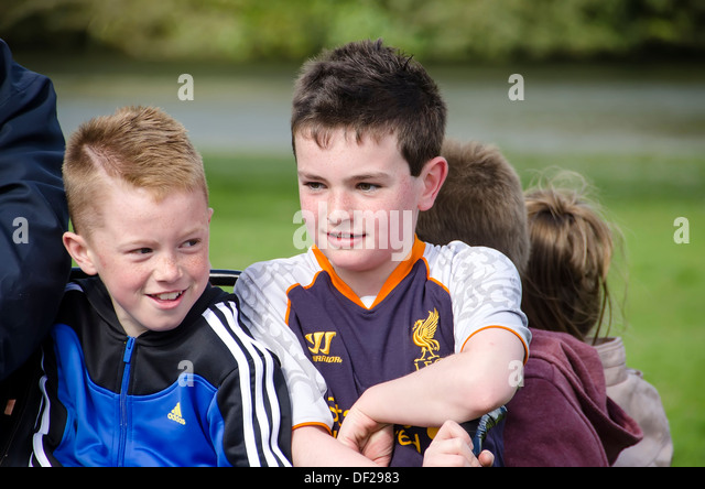 Two freckled and smiling Irish boys taking a ride in pony cart with other kids, Castlemartyr, Ireland. - Stock Image