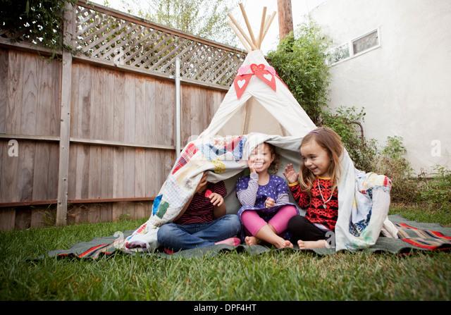 Three young girls in garden hiding under blanket - Stock Image