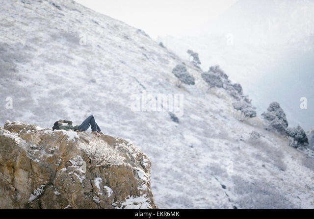 A man, a hiker in the mountains, taking a rest lying on a rock outcrop above a valley. - Stock Image