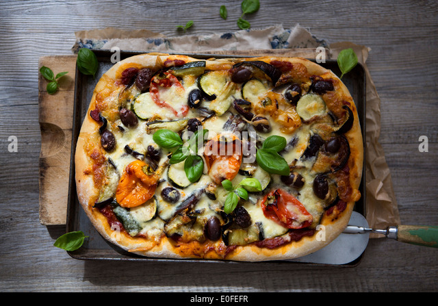 Homemade Roasted Vegetable Pizza with Olives, Basil and Peppers - Stock Image