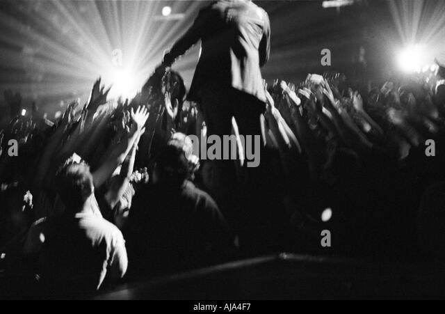 Bono reaches out to members of the audience at a U2 concert - Stock Image