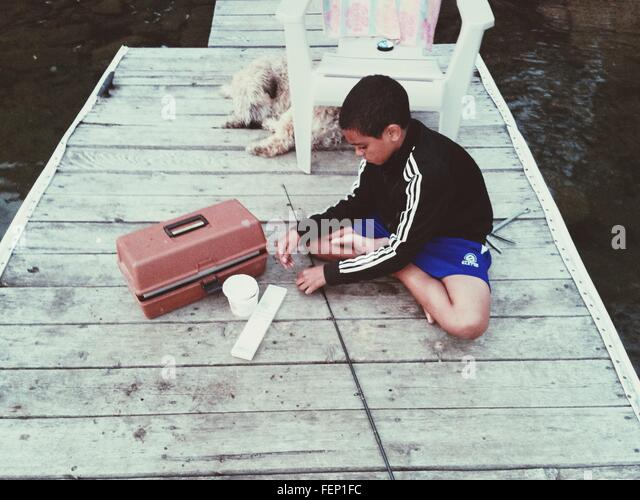 Boy Sitting With Fishing Rod On Jetty - Stock Image