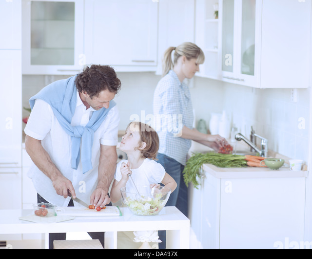 Father and Daughter looking at each other whilst preparing healthy meal in kitchen - Stock Image