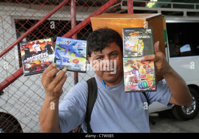 Managua Nicaragua Latin America Pista Juan Pablo II street vendor informal economy Hispanic man indigenous DVD movies - Stock Image