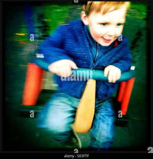 A young boy having fun on a swing at the play park - Stock Image