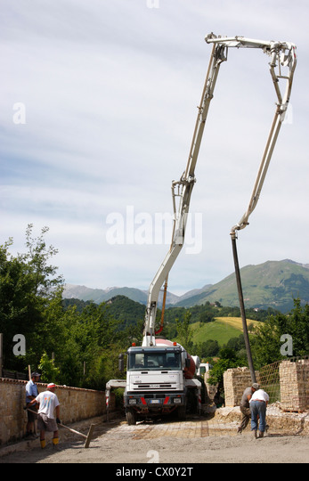 Cement being delivered  by a lorry using an 'elephant pipe',and worked into a foundation in Le  Marche ,Italy - Stock Image