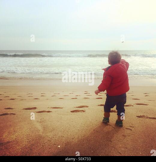 Child throwing stones into the sea in Portugal , Algarve - Stock Image