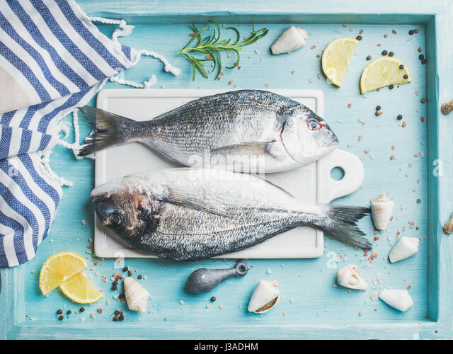 Fresh Sea bream or dorado raw uncooked fish with seasoning on white board over turquoise blue tray background, top - Stock Image