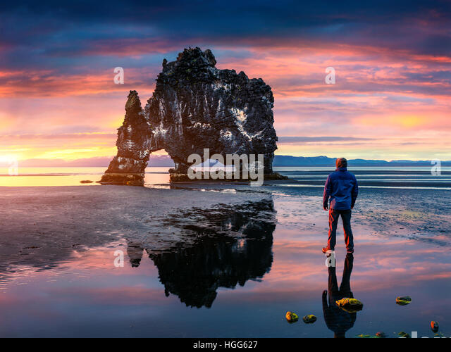 Man stands on the surface of water at fall of tide and and admiring of sunrise. Huge basalt stack Hvtserkur on the - Stock Image
