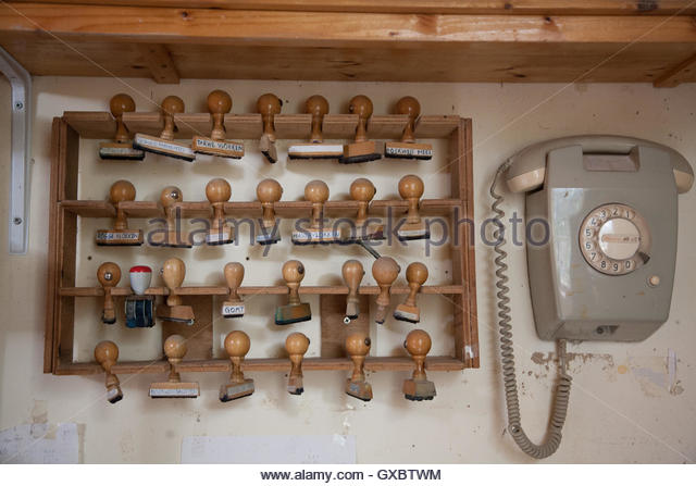 Stamps for grain types milled in Dutch with vintage telephone inside Windmill, Gouda, South Holland, The Netherlands. - Stock Image