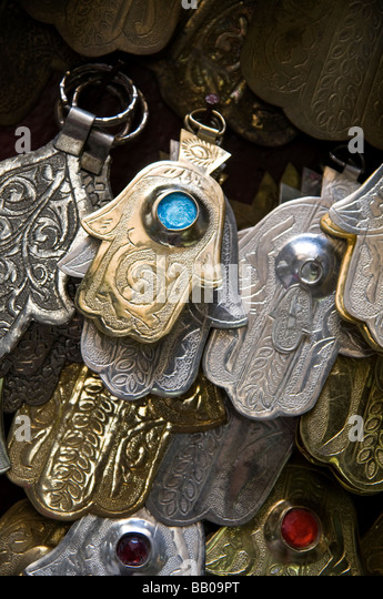 Dozens of Khamsa - or Fatima's hands. Hanging for sale at market stall in the medina, Fez, Morocco - Stock Image