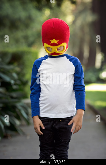 little boy wearing red and yellow superhero mask posing outside on the sidewalk, obscuring his eyes - Stock Image