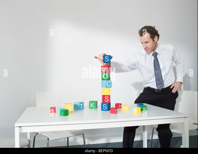 Business man playing with blocks - Stock Image