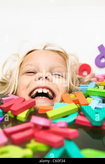 Laughing child playing with foam letters - Stock Image