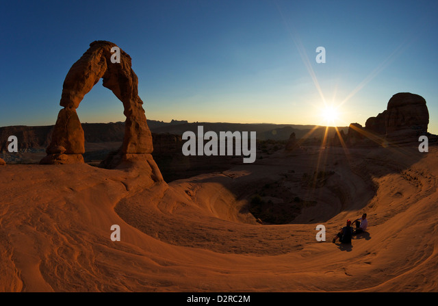 Two men sitting, Delicate Arch, Arches National Park, Moab, Utah, United States of America, North America - Stock Image