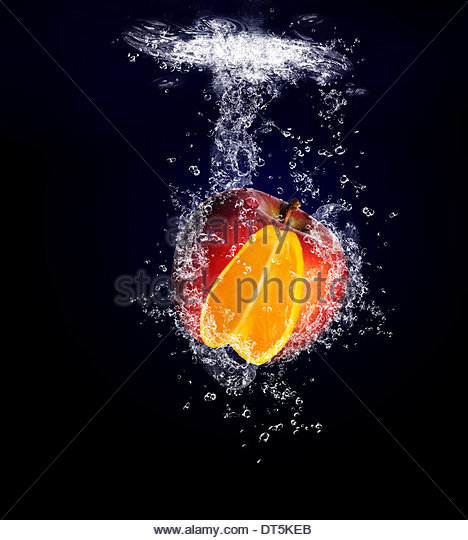 Unusual And Unique Image Of An Apple With A Orange Centre, Diving Underwater Into A Pool Of Water In Healthy Eating - Stock Image