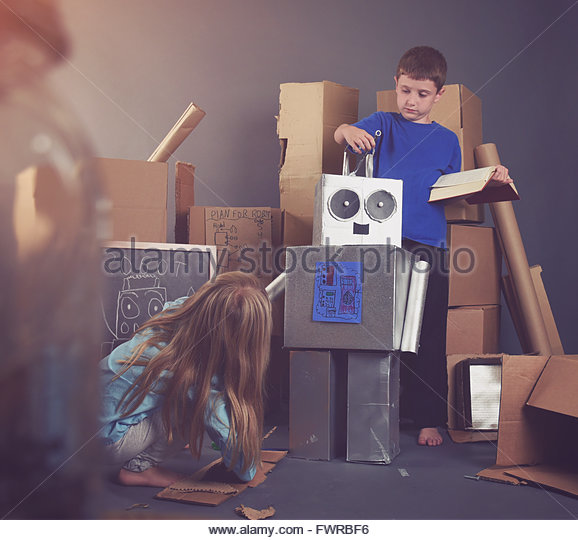 Two Children are building a metal robot with tools and books for an imagination, science or education concept. - Stock Image