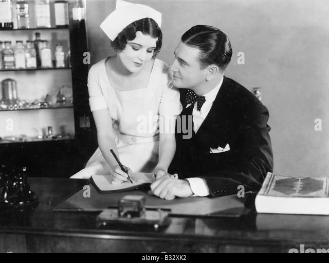 Nurse sitting on the doctor's lap - Stock Image