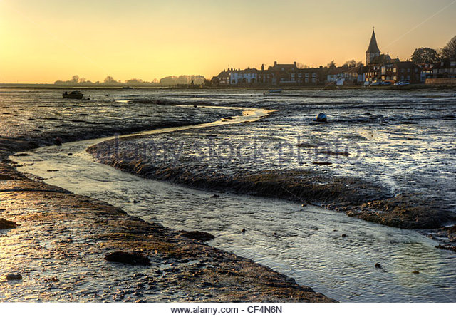 Sunset view across the mudflats at Bosham Harbour at low tide. - Stock Image