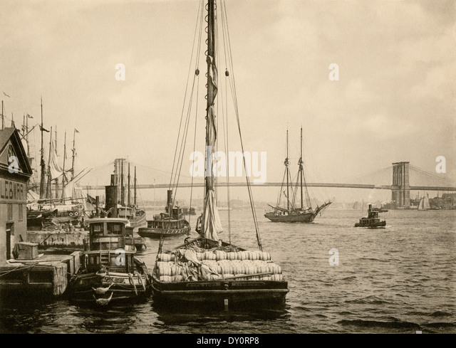Waterfront of the East River, Brooklyn Bridge in the background, 1890s. - Stock Image