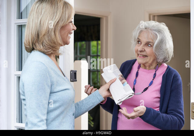 Woman Delivering Newspaper To Elderly Neighbour - Stock Image