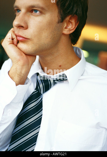 Businessman with hand under chin, portrait - Stock Image
