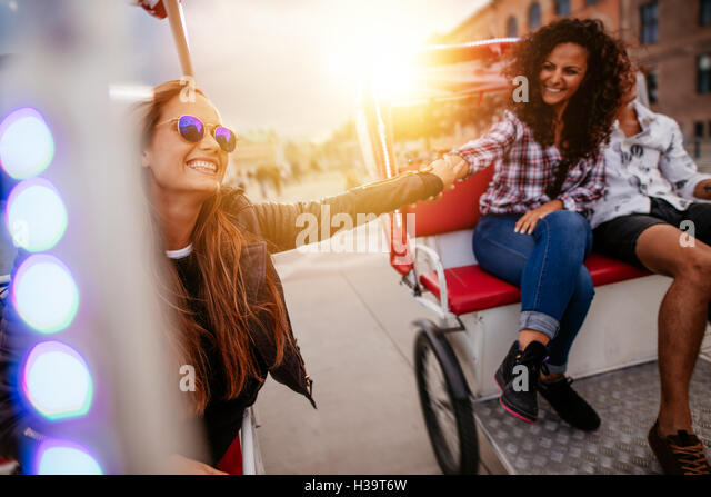Best friends enjoying tricycle ride in the city. Teenage girls riding on tricycles and holding hands. - Stock Image