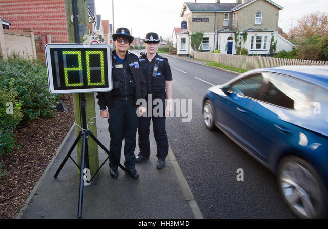 Two women police officers, a speed indicator and a passing car. - Stock Image
