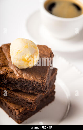 Brownie with ice cream and a cup of coffee on the table vertical - Stock Image